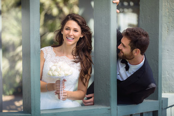 Playful bride and groom couple laugh and smile together, happy and in love wedding day
