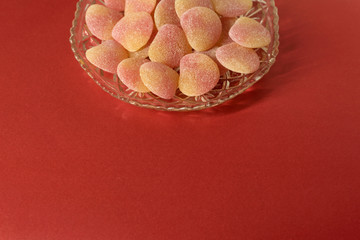 Sugared jelly sweets in crystal cut glass dish - on minimal red background - centred design element, copy space