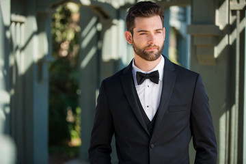 Stylish attractive and masculine groom standing alone, well dressed, modern and sleek