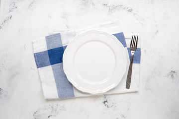 Empty white plate and fork on a table, top view
