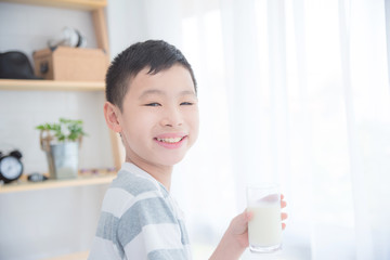 Young asian boy holding a glass of milk and smiling at camera