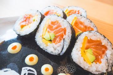Closeup of sushi roll with salmon and avocado on plate