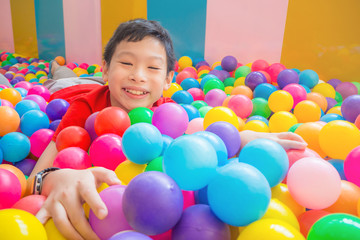 Young asian boy smiling while lying on many color balls at indoors playground