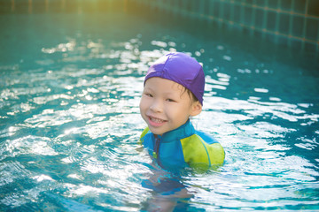 Little asian girl in swimming suit smiling in swimming pool