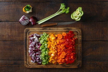 Chopped vegetables arranged on cutting board on wooden table, top view
