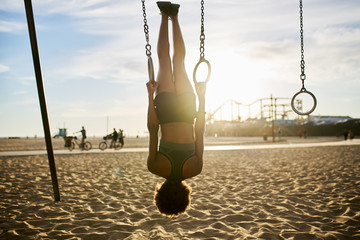 fit african american woman flipping upside down on gymnastic rings at exercise park