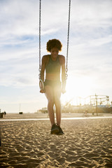 fit african american woman using gynastic rings on beach  exercise equipment