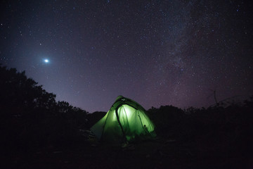 Milky way and moon on the night sky above field with dark grass and tent