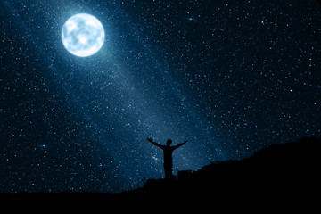 Silhouette of happy man enjoying the night with moon and stars