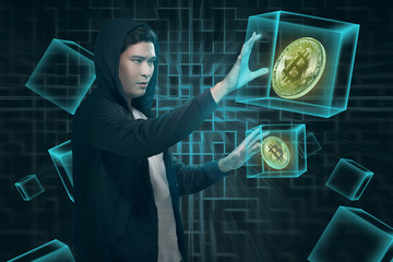 Attractive asian man in hoodie with digital bitcoin