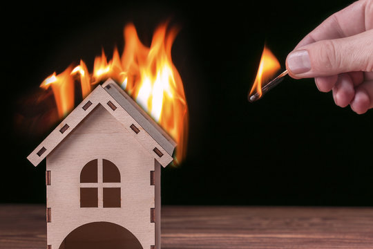 House fire concept. Toy house with flames and hand with matchstick.