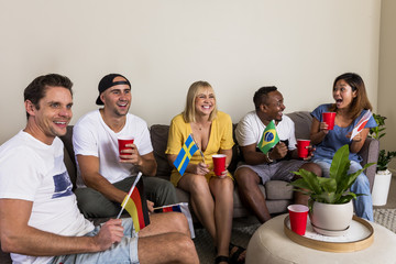 Group of young multinational sports fans socializing and watching TV
