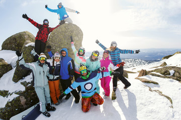 Group of friends snowboarders having fun on the top of mountain