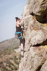 women climbing a rock wall