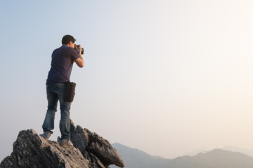 Man standing and taking photos of mountain view on the peak. outdoor activity and photography concept