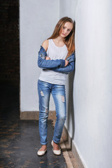 Fashion teenager girl standing leaning back against a white wall. Young caucasian woman model in casual stylish clothes, denim jacket, white singlet cotton, youth jeans. High fashion urban style.