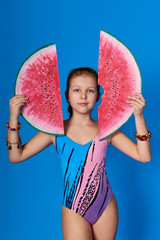 Cute face girl in swimsuit holding 2 piece red watermelon. Summer portrait caucasian teenager in studio isolated on a blue background. Concept lovely summertime,recreation,break,vacation,travel.