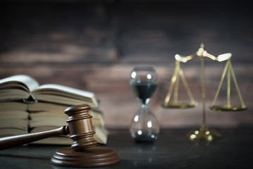 Law and Justice concept. Gavel of the judge, books, scales of justice. Brown background,  Courtroom theme.