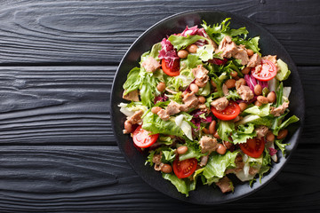 Healthy hearty salad of tuna, borlotti beans, tomatoes, lettuce close-up on a plate. horizontal top view