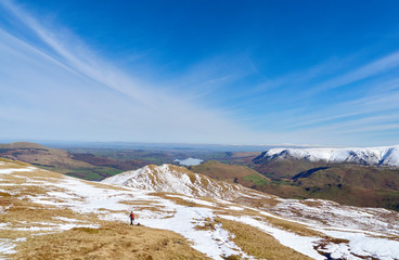 A female hiker descending from a snow covered Place Fell summit in the English Lake District.
