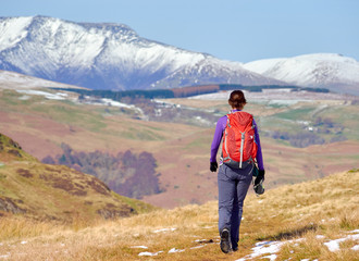 A female hiker descending from a snow covered Place Fell summit with Blenccathra in the English Lake District.