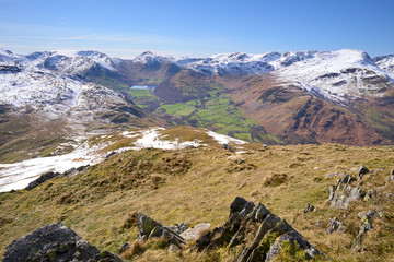Snow covered mountains of Stony Cove, Red Screes, Fairfield and Brothers Water lake from Place Fell in the Lake District, England, UK.