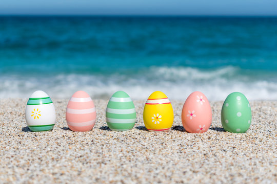 Colorful Easter eggs on the beach in sunny day. Easter concept.