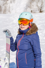 Photo of sporty woman wearing helmet with snowboard