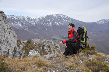 Hiker enjoy in a view on mountain range. Young man high in mountain in spring time.