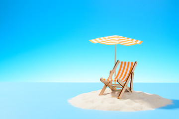 The concept of a tropical vacation. A chaise longue under an umbrella on the sandy island. Sky with copy space