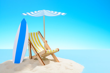 The concept of a tropical vacation. A chaise longue under an umbrella and surfboard on the sandy island. Sky with copy space