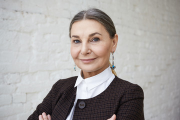 Beauty, style, fashion and age concept. Close up portrait of positive elegant 50 year old female with gray hair and wrinkled face posing against white brick wall background and smiling at camera