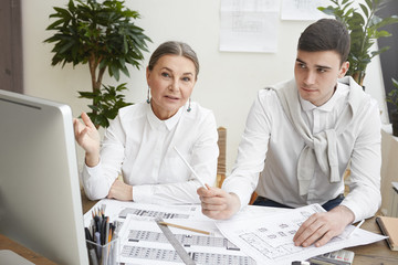 Candid shot of stylish experienced gray haired senior female architect pointing at computer screen, explaining point of view to her young male colleague while working on new housing project together,