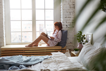 Sideways shot of cheerful young female in nightsuit sitting barefooted on wide windowsill with portable computer on her lap, urban landscape outside and undone bed in foreground. Selective focus