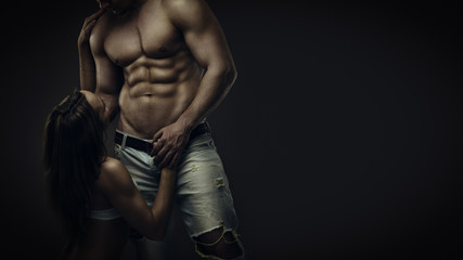 Fitness couple. Artistic portrait of young athletic  shirtless man and woman in underwear in studio