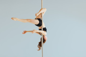 Beautiful pole dancer performing in the studio. Seria photo of middle aged red hair woman in black bra and shorts workout pole dance on air with different poses. Gray background.