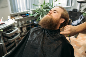 handsome young bearded guy sitting in an armchair in a beauty salon