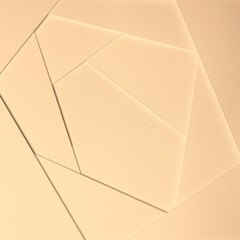 Abstract geometric background in light pastel tones from sheets of thick pale yellow, beige paper, cardboard.