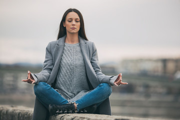 Young woman is meditating after work on cloudy day.