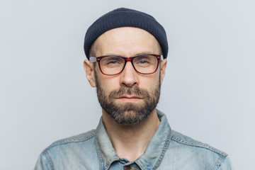 Photo of intelligent confident stylish man with dark thick beard and mustache, looks seriously into camera, poses against grey studio background, wears spectacles and hat. Facial expressions concept