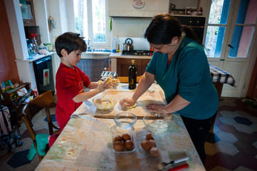 mother with 5 year old son in the kitchen prepare with eggs and flour, homemade pasta