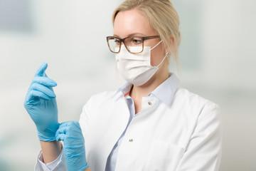 Junge Ärztin mit Mundschutz zieht medizinische Handschuhe an