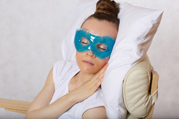Young lady is keeping eye gel mask.