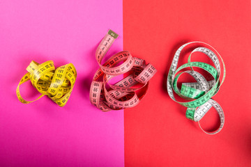 Three measuring tape on red and pink background.