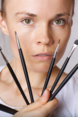 Young lady keeps make up brushes kit close to her face. Closeup