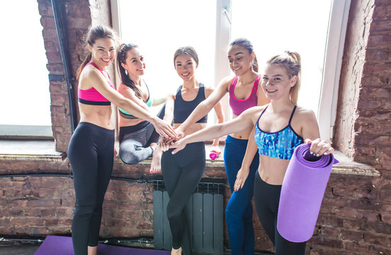 Rest after workout. Group of young beautiful smiling sports women in sports clothes after fitness or yoga fun and talk at the window. Girlfriends holding hands together