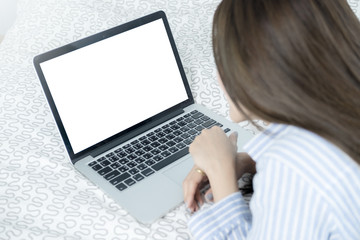 Young woman with blank white screen laptop computer on the bed.