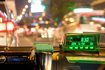The digital taxi meter on the dashboard of cab shows kilometer and cost. Night taxi ride in traffic jam.