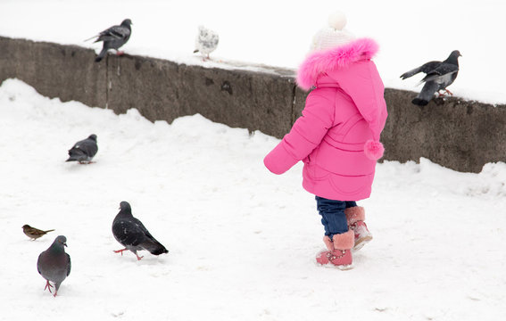 A little girl chasing pigeons in the winter
