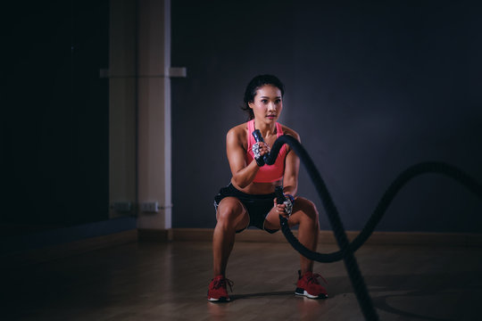 Asia women exercising with battle ropes at gym.